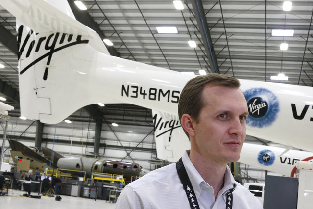 Virgin Galactic's CEO George T. Whitesides stands in front of their new spaceship N202VG (bottom L) and the WhiteKnightTwo carrier aircraft mothership, which landed safely after splitting from SpaceShipTwo, in a hangar at Mojave Air and Space Port in Mojave. (Photo by Lucy Nicholson/Reuters)