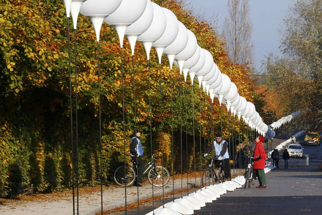"""People look at stands with balloons placed along the former Berlin Wall location at Mauerpark, which will be used in the installation """"Lichtgrenze"""" (Border of Light) in Berlin November 7, 2014. (Photo by Pawel Kopczynski/Reuters)"""