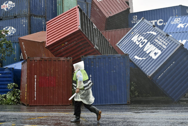 A man walks past downed shipping containers at the Kaohsiung Harbour as typhoon Meranti lashed southern Taiwan on September 14, 2016. Parts of Taiwan were brought to a standstill September 14 as super typhoon Meranti skirted past the island's southern tip, bringing the strongest winds in 21 years and disrupting traffic ahead of a major holiday. (Photo by Sam Yeh/AFP Photo)