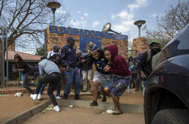 Protesters run for cover as they clash with police at Eldorado Park police station in Johannesburg, South Africa, Thursday, August 27, 2020. Residents from the township, south of Johannesburg are demanding justice for a teenager shot and killed, allegedly at the hands of police Wednesday. (Photo by Themba Hadebe/AP Photo)
