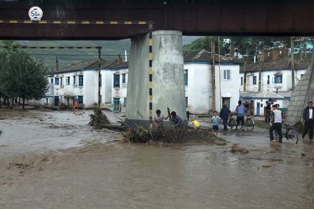 """Residents attempt to clear flood debris from under a bridge in the city of Rajin in North Korea in this August 22, 2015 picture taken by a recent visitor. Heavy rain in North Korea killed 40 people, stranded thousands in flash floods and caused """"massive"""" damage on the weekend, the International Federation of the Red Cross and North Korean media said. (Photo by Reuters/Stringer)"""