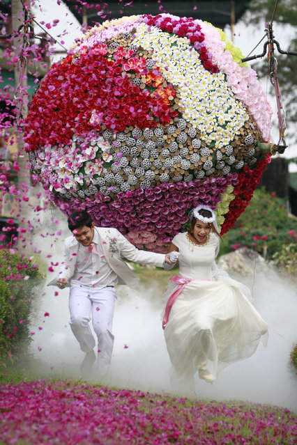 Prasit Rangsitwong, left, and Varutton Rangsitwong run away from a giant flower ball as a part of an adventure-themed wedding ceremony in Prachinburi province, Thailand, Wednesday, February 13, 2013, on the eve of Valentine's Day. (Photo by Wason Wanichakorn/AP Photo)