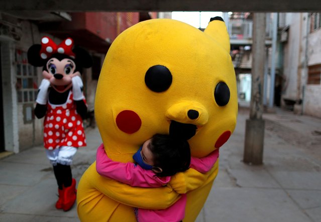 A volunteer wearing a costume of Pokemon character Pikachu hugs a child during Children's Day, amid the coronavirus disease (COVID-19) outbreak, in Fuerte Apache, in Buenos Aires, Argentina on August 16, 2020. (Photo by Agustin Marcarian/Reuters)