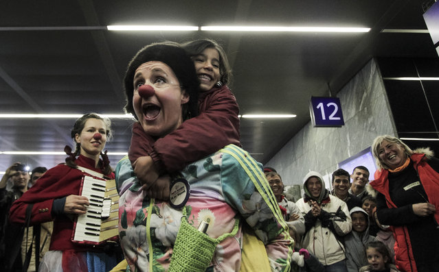 "Members of the ""Red Nose Clown doctors"" perform for migrants at the Main Train Station in Vienna, Austria on October 15, 2015. (Photo by Patrick Domingo/AFP Photo)"