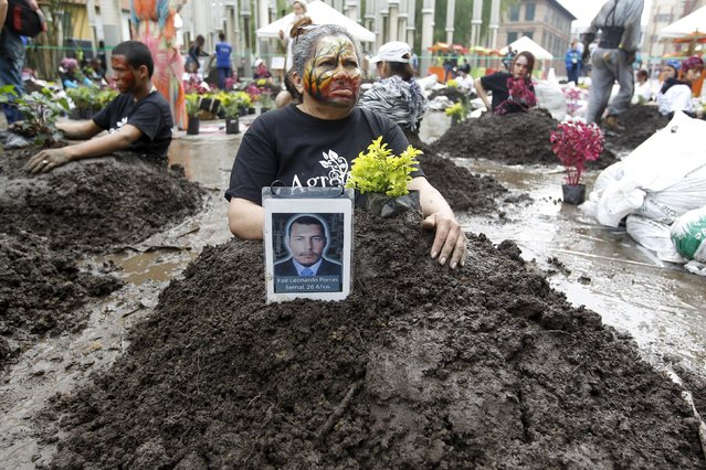 Protesters sit with mock graves of the disappeared during a protest against Colombian army's Operation Orion, a 2002 military operation in the Comuna 13 neighborhood, in Medellin October 16, 2015. The operation against paramilitary groups and militias in an urban area killed at least 650 victims and left at least 92 missing, or disappeared, according to local media. (Photo by Fredy Builes/Reuters)