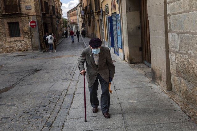 An elderly man wearing a face mask to prevent the spread of coronavirus walks in downtown Segovia, central Spain, Saturday, September 19, 2020. Spain has been the hardest hit European country in the second wave of the pandemic. (Photo by Bernat Armangue/AP Photo)