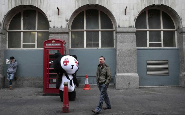 A man walks past a person wearing a panda costume on Gerrard Street in London's Chinatown, Britain October 19, 2015. Chinese President Xi Jinping arrives in Britain on Monday for a state visit at the invitation of Queen Elizabeth II, the first state visit to the United Kingdom by a Chinese leader since 2005. (Photo by Suzanne Plunkett/Reuters)