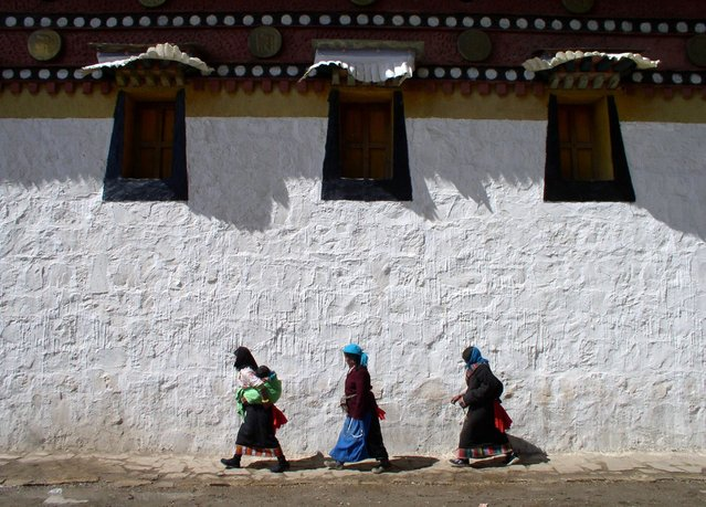 Tibetans walking a kora (spiritual circuit) around a Buddhist temple in southern Gansu. (Photo by Tom Carter/The Atlantic)