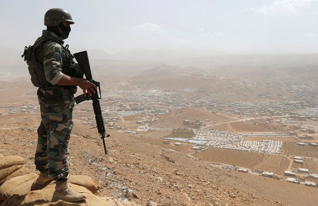 A Lebanese soldier carries his weapon as he stands on sandbags at an army post in the hills above the Lebanese town of Arsal, near the border with Syria, Lebanon September 21, 2016. (Photo by Mohamed Azakir/Reuters)