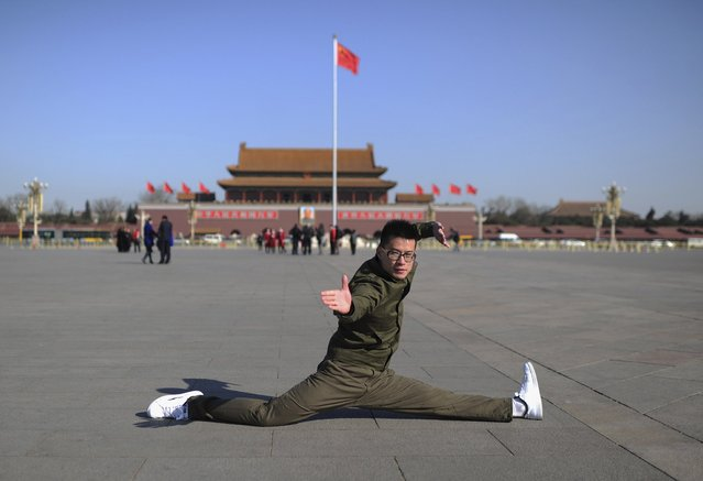 A hotel security guard poses for pictures in front of China's national flag at Tiananmen Square during the third plenary session of the National People's Congress (NPC) in Beijing March 10, 2013. (Photo by Stringer/Reuters)
