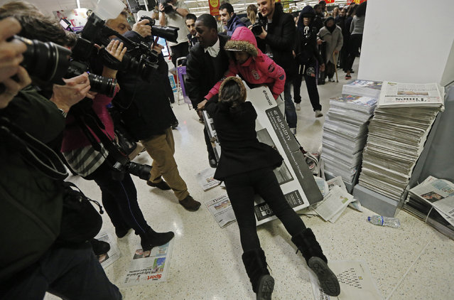 Shoppers wrestle over a television as they compete to purchase retail items on Black Friday at an Asda superstore in Wembley, north London November 28, 2014. (Photo by Luke MacGregor/Reuters)