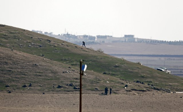 Three Islamic State fighters pray (bottom) as another runs to the top of a hill in the outskirts of Syrian town of Kobani, as seen from the Mursitpinar crossing on the Turkish-Syrian border in the southeastern town of Suruc, in Sanliurfa province, in this October 23, 2014 file photo. (Photo by Kai Pfaffenbach/Reuters)
