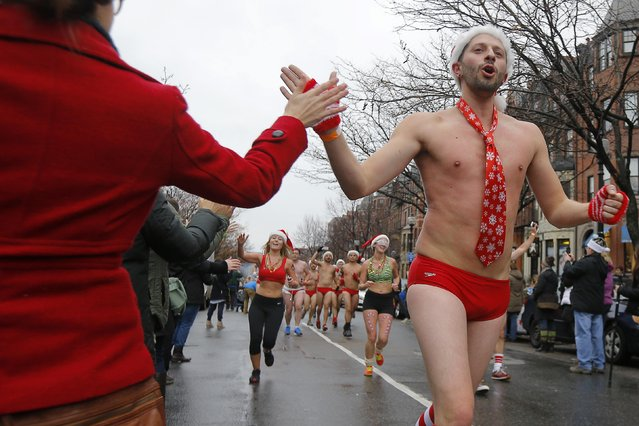 Onlookers high five runners taking part in the 15th annual Santa Speedo Run, a charity run through the streets of the Back Bay, in Boston, Massachusetts December 6, 2014. (Photo by Brian Snyder/Reuters)