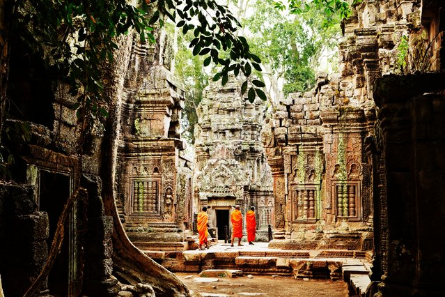 Monks clad in orange robes wander amid the crumbling temple ruins of Ta Prohm in Cambodia. (Photo by Mark Read/Lonely Planet)