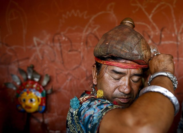 A Nepalese devotee prepares for a religious mask performance during the Seekaali Festival in Khokna village, near Kathmandu, Nepal, 07 October 2016. During the 300-year-old Seekali festival, elderly ethnic Newari devotees wear masks of 14 various goddesses including Lord Ganesha, Lord Shiva, Lord Laxmi, Lord Brahma and Lord Bishnu. The Khokna people celebrate the Seekaali festival as an alternative of the Dashain festival which is biggest festival of Nepalese Hindus that celebrates the victory of the gods over demons. (Photo by Narendra Shrestha/EPA)