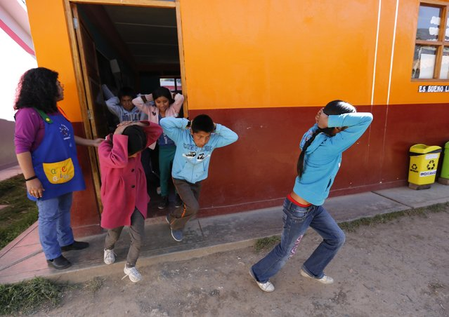 School children evacuate a school during an earthquake and avalanche drill in Ancash November 28, 2014. World greenhouse gas emissions are rising fast and it may be years before they start falling, prompting glaciologists to urge Peru to act fast to protect towns and villages in danger. (Photo by Mariana Bazo/Reuters)