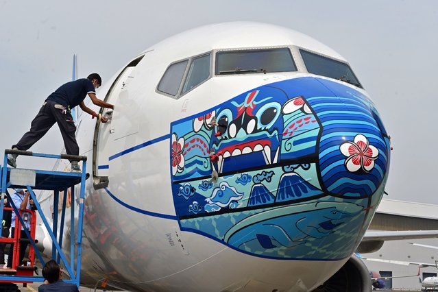 A worker closes a door of a Garuda Indonesia Boeing 373-800 NG with a new face mask design as part of a campaign to promote the wearing of face masks amid the Covid-19 coronavirus, at the airport in Tangerang on October 12, 2020. (Photo by Adek Berry/AFP Photo)