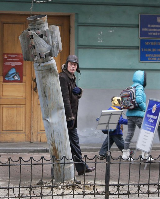 People pass by an unexploded missile shot by pro-Russian separatists in the country's east and brought to the Ukrainian capital as a symbol of the current conflict, in downtown Kiev, Ukraine, Tuesday, December 16, 2014. (Photo by Efrem Lukatsky/AP Photo)
