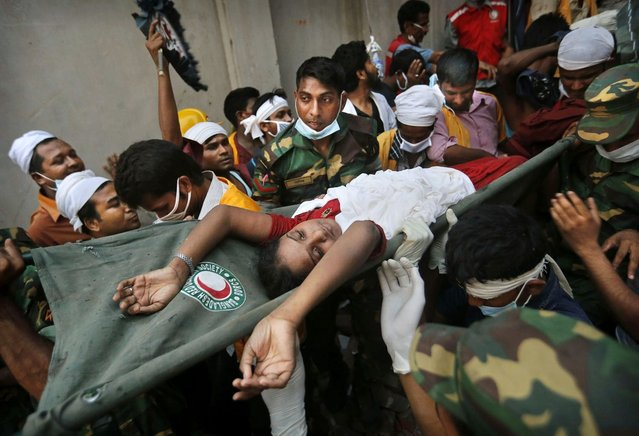 A Bangladeshi woman survivor is carried from the rubble by rescuers at the site of a building that collapsed Wednesday in Savar, near Dhaka, Bangladesh, Thursday, April 25, 2013. By Thursday, the death toll reached at least 194 people as rescuers continued to search for injured and missing, after a huge section of an eight-story building that housed several garment factories splintered into a pile of concrete. (Photo by Kevin Frayer/AP Photo)