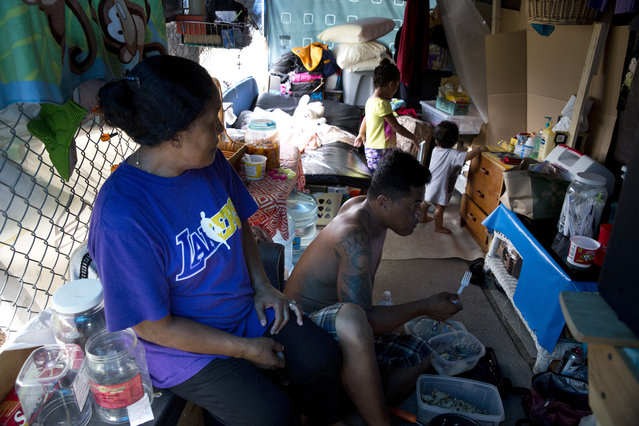 In this Monday, August 24, 2015 photo, Kionina Kaneso, left, and her boyfriend, Racly Rufes, rest in their tent at a homeless encampment in the Kakaako district of Honolulu. Kaneso, 59, moved to Hawaii from Chuuk in Micronesia to find better medical care for her son, who has a heart condition. But instead of finding a better life, she wound up living in one of the nation's largest homeless encampments with her boyfriend, daughter and three grandchildren. (Photo by Jae C. Hong/AP Photo)