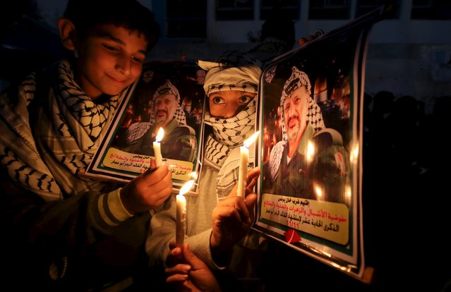 Palestinian boys light candles during a protest marking the 11th anniversary of Palestinian leader Yasser Arafat's death, in Khan Younis in the southern Gaza Strip November 11, 2015. Arafat died on November 11, 2004. (Photo by Ibraheem Abu Mustafa/Reuters)
