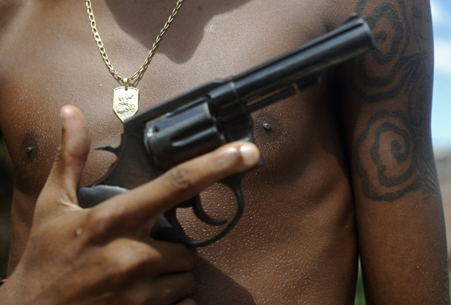 A Brazilian drug gang member nicknamed Giant, 17, poses with a gun and his medallion of St. George, in a slum in Salvador, Bahia State, April 11, 2013. One of Brazil's main tourist destinations and a 2014 World Cup host city, Salvador suffers from an unprecedented wave of violence with an increase of over 250% in the murder rate, according to the Brazilian Center for Latin American Studies (CEBELA). (Photo by Lunae Parracho/Reuters)