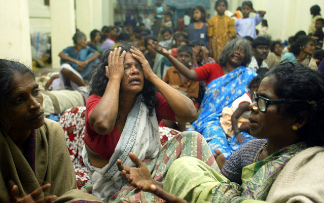 In this December 27, 2004 file photo, people displaced by the tsunami mourn their losses as they sit inside a relief camp at a temple in Varichikudi, about 200 kilometers (125 miles) south of Madras, India. (Photo by Gurinder Osan/AP Photo)