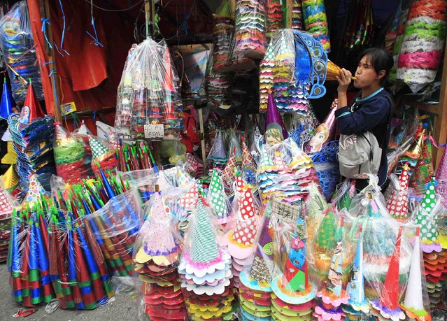 A vendor blows a paper horn to attract customers at a market in Manila December 30, 2014. Horns, which cost around 50 pesos ($1.13) to 150 pesos  ($3.40) a piece, are popular alternative noise makers to dangerous firecrackers during the New Year revelry. (Photo by Romeo Ranoco/Reuters)