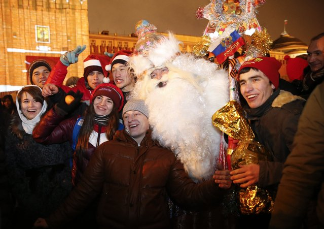 Revellers pose for a picture with a man dressed as Father Frost, the equivalent of Santa Claus, during celebrations of New Year's Day in Red Square in Moscow December 31, 2014. (Photo by Tatyana Makeyeva/Reuters)