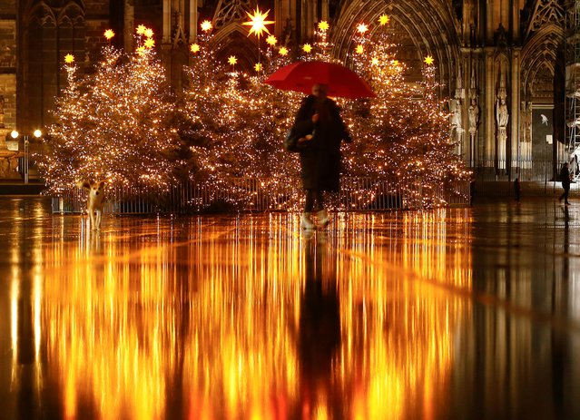 A woman walks on a square decorated with Christmas trees in front of the famous Cologne cathedral during lockdown in Cologne, Germany, December 21, 2020. (Photo by Thilo Schmuelgen/Reuters)