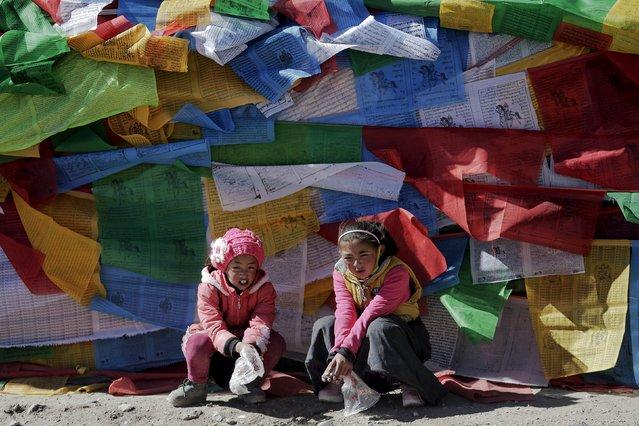 Tibetan girls sit in front of prayer flags at Namtso lake in the Tibet Autonomous Region, China November 18, 2015. (Photo by Damir Sagolj/Reuters)