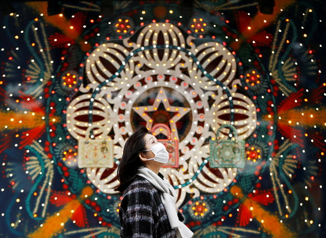 A woman wearing a protective face mask walks past Christmas decorations, amid the coronavirus disease (COVID-19) outbreak, at Ginza shopping district in Tokyo, Japan on December 19, 2020. (Photo by Issei Kato/Reuters)