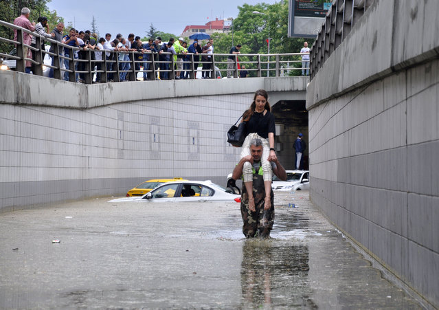 A man carries a woman on his shoulders at a flooded street after heavy rain in Ankara, Turkey May 20, 2018. (Photo by Dogan News Agency via Reuters/DHA)