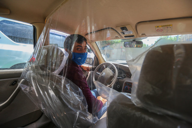 A taxi driver wearing a mask to protect sits inside a transparent partition to isolate himself from passengers on May 7, 2020 in Baku, Azerbaijan. The coronavirus outbreak has infected more than 3 million people across the world. Azerbaijan has reported 2127 cases of COVID-19 and 28 deaths. (Photo by Aziz Karimov/Getty Images)