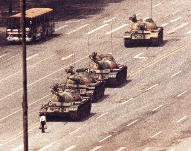 A man stands in front of a convoy of tanks in the Avenue of Eternal Peace, Tiananman Square in Beijing, June 5, 1989 in protest of the thousands of pro-democracy student demonstrators that were massacred the previous day by Chinese Troops. (Photo by Arthur Tsang/Reuters)