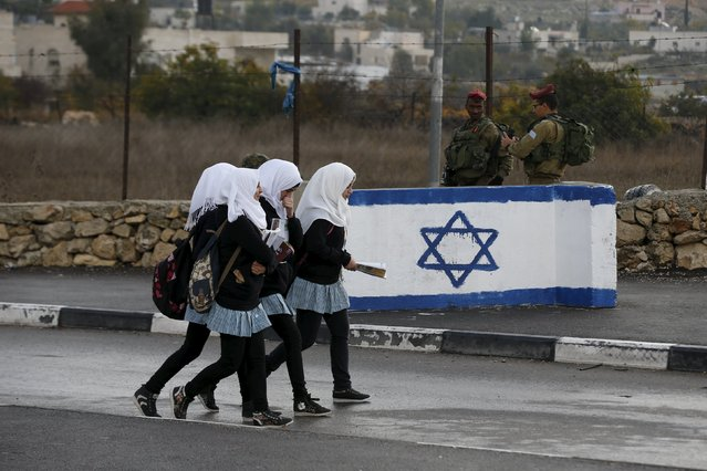 Palestinian school girls walk past Israeli soldiers at a checkpoint at a entrance to the village of Beit Einun near the West Bank city of Hebron December 1, 2015. (Photo by Baz Ratner/Reuters)