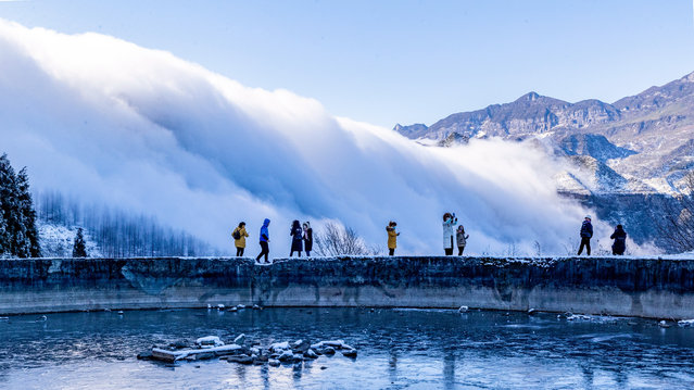 Tourists watch as clouds drift over the Jinfo (Golden Buddha) Mountain after a snowfall on January 18, 2021 in Chongqing, China. (Photo by Qu Mingbin/VCG via Getty Images)