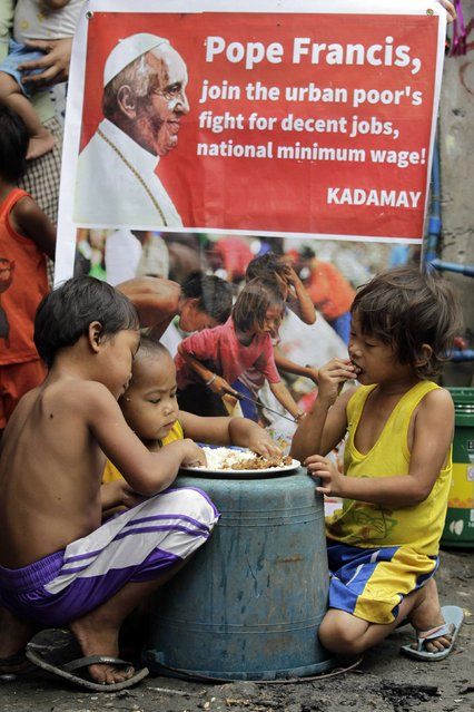 "Children eat ""pagpag"", re-cooked leftover food scavenged from trash, in front of a poster addressed to Pope Francis at a slum area in Quezon city, metro Manila January 13, 2015. (Photo by Romeo Ranoco/Reuters)"