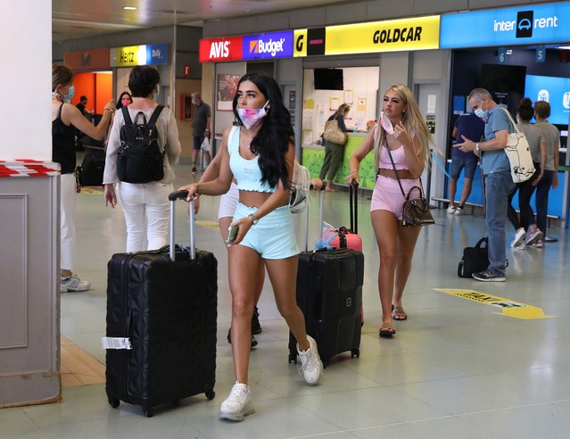 Tourists leave the arrivals area of Ibiza airport on July 28, 2020 in Ibiza, Spain. The United Kingdom, whose citizens comprise the largest share of foreign tourists in Spain, added Ibiza and other Spanish islands to its advice against non-essential travel to the country, citing a rise in coronavirus cases. The change follows the UK's decision to reimpose a 14-day isolation period for travelers returning from Spain. (Photo by Isabel Infantes/The Sun)