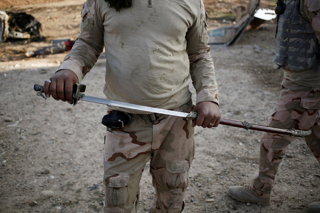 An Iraqi soldier holds up a sword he found, which he says is similar to the kind used by Islamic State militants for beheadings, at the front line in the Intisar disrict of eastern Mosul, Iraq November 4, 2016. (Photo by Zohra Bensemra/Reuters)
