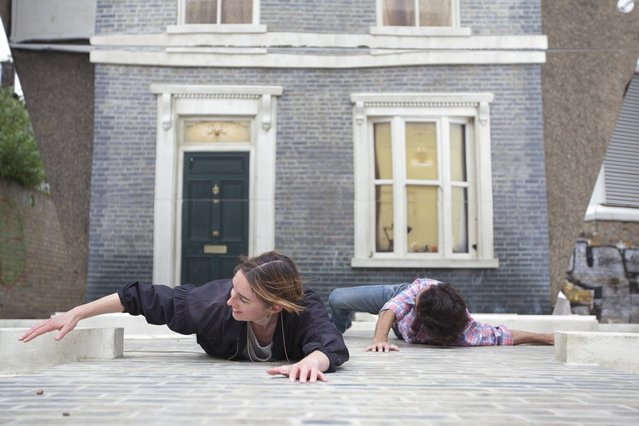 "People appear dangling as a large-scale installation art piece by Leandro Erlich, named ""Dalston House"", is displayed on June 24, 2013 in London, England. Part of the ""Beyond Barbican"" summer series of events, the interactive installation is a full facade of a late nineteenth-century Victorian terraced house built on the ground with a large mirror above it to reflect people as to appear dangling from the structure.  (Photo by Dan Dennison/Getty Images)"
