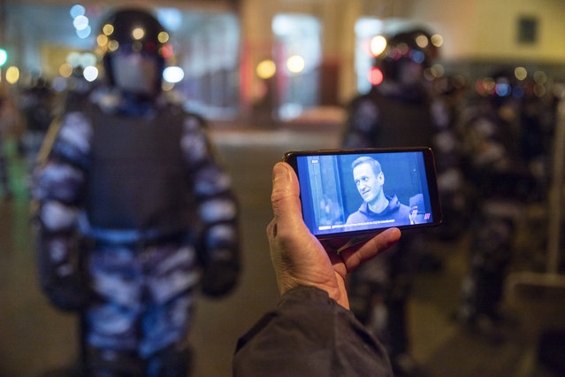 A journalist watches a live stream of a court hearings with the Russian opposition leader Alexei Navalny on a screen as Russian Rosguardia (National Guard) soldiers guard in front of the court in Moscow, Russia, Tuesday, February 2, 2021. A Moscow court has ordered Russian opposition leader Alexei Navalny to prison for more than 2 1/2 years on charges that he violated the terms of his probation while he was recuperating in Germany from nerve-agent poisoning. Navalny, who is the most prominent critic of President Vladimir Putin, had earlier denounced the proceedings as a vain attempt by the Kremlin to scare millions of Russians into submission. (Photo by Pavel Golovkin/AP Photo)