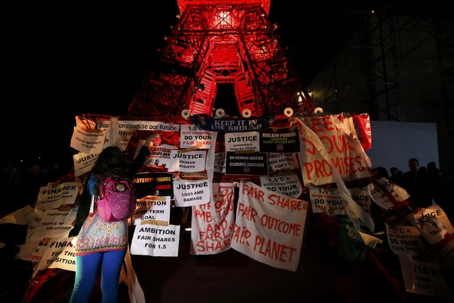 A woman fixes a sign during a demonstration in front a replica of the Eiffel Tower at the World Climate Change Conference 2015 (COP21) at Le Bourget, near Paris, France, December 9, 2015. (Photo by Stephane Mahe/Reuters)