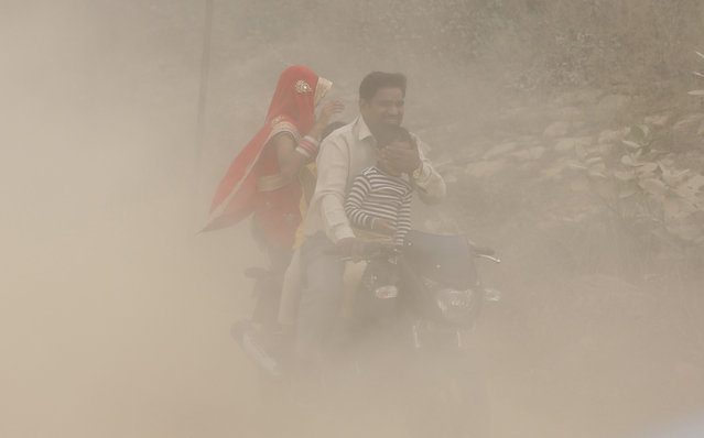 An Indian man and his family ride a bike during heavy dust and smog in New Delhi, India, 06 November 2016. People in India's capital city are struggling with heavily polluted air after smoke released from fireworks set off during the Diwali celebrations last weekend still lingers in the air of the metropolis. The air has forced many local schools – especially those run by the government – to close for the day and the Delhi government put a ban on construction and demolition works for five days. Visibility in the city has been reduced to 400 meters as Delhi pollution levels rose to 15 times more then the safe limit, a news reports said. (Photo by Harish Tyagi/EPA)