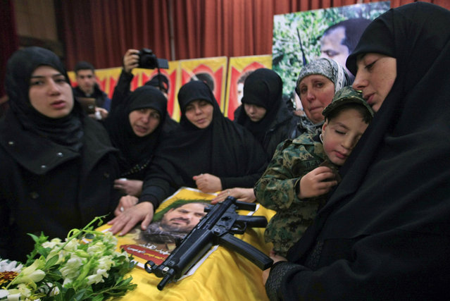 The sister of Hezbollah member Mohammad Issa who was killed in an Israeli airstrike in Syria on Sunday, holds his son Ahmed as she mourns over his coffin  during his funeral procession, in the southern village of Arab Salim, Lebanon, Tuesday, January 20, 2015. Hezbollah has accused Israel of carrying out Sunday's airstrike, which occurred on the Syrian side of the Golan Heights and killed six members of the Lebanese militant group and an Iranian general. (Photo by Mohammed Zaatari/AP Photo)