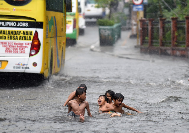 Children play on a flooded highway during a summer downpour in Edsa, Quezon city, metro Manila, Philippines on April 25, 2018. (Photo by Dondi Tawatao/Reuters)