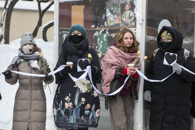 Women hold flowers and a white ribbon as they stand in a line during a rally in support of jailed opposition leader Alexei Navalny and his wife Yulia Navalnaya at Arbat street in Moscow, Russia, Sunday, February 14, 2021. (Photo by Pavel Golovkin/AP Photo)