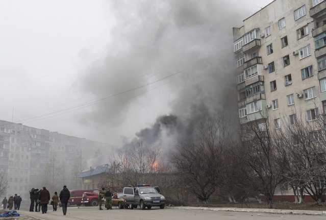 Smoke and flames rise above a burning building after shelling in the eastern Ukrainian city of Mariupol, 24 January 2015. Fifteen civilian people were killed and 46 injured during a shelling at Jan.24 morning in Mariupol according to a UNIAN agency report. (Photo by Sergey Vaganov/EPA)
