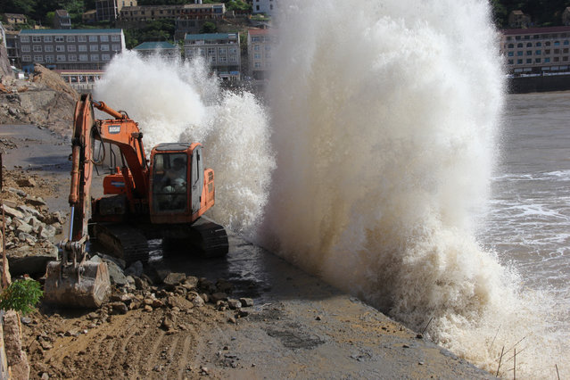 A wave breaks on the waterfront next to an excavator, as super typhoon Maria approaches, in Taizhou, Zhejiang province, China on July 10, 2018. (Photo by Reuters/China Stringer Network)