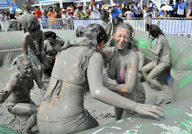Tourists play with mud during the 16th Boryeong mud festival at Daecheon swimming beach in Boryeong, 150 kilometers southwest of Seoul, on July 20, 2013. The annual festival which runs from July 19-28 aims to encourage the use of mud for cosmetic skin-care and to promote tourism in the region. (Photo by Jung Yeon-Je/AFP Photo)